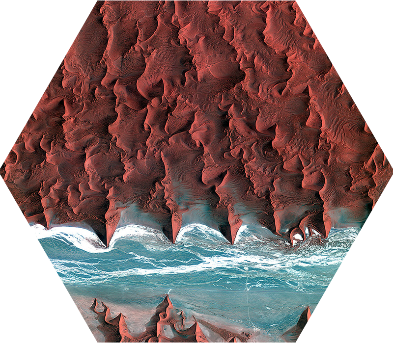 An image of the Sahara desert as seen from above. A small section of the ocean crosses through the desert dunes.